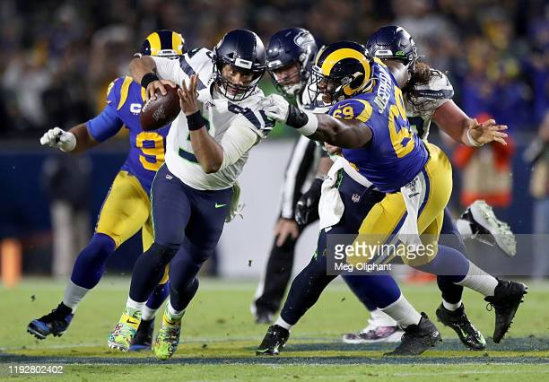 Quarterback Russell Wilson of the Seattle Seahawks scrambles against defensive tackle Sebastian Joseph-Day of the Los Angeles Rams during the game at...