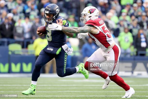 Quarterback Russell Wilson of the Seattle Seahawks scrambles against linebacker Cassius Marsh of the Arizona Cardinals during the game at CenturyLink...