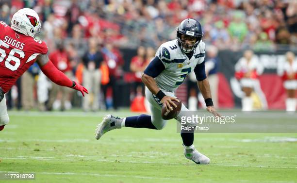 Quarterback Russell Wilson of the Seattle Seahawks scrambles away from linebacker Terrell Suggs of the Arizona Cardinals during the first half of the...