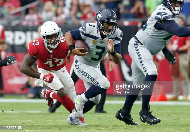Quarterback Russell Wilson of the Seattle Seahawks scrambles away from linebacker Haason Reddick of the Arizona Cardinals during the second half of...