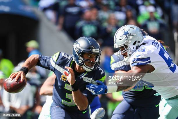 Quarterback Russell Wilson of the Seattle Seahawks scrambles during the first quarter against the Dallas Cowboys at CenturyLink Field on September 23...