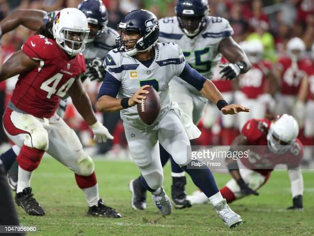 Quarterback Russell Wilson of the Seattle Seahawks scrambles out of the pocket away from defensive end Markus Golden of the Arizona Cardinals during...