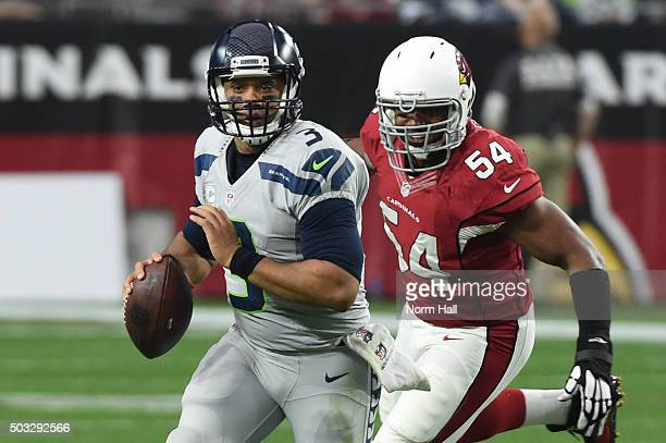 Quarterback Russell Wilson of the Seattle Seahawks scrambles with the football in front of inside linebacker Dwight Freeney of the Arizona Cardinals...