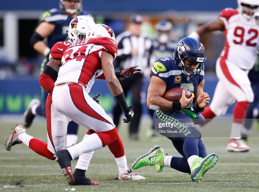 Quarterback Russell Wilson #3 of the Seattle Seahawks slides after rushing for 31 yards against the Arizona Cardinals in the second half at CenturyLink Field on December 31, 2017 in Seattle, Washington.
