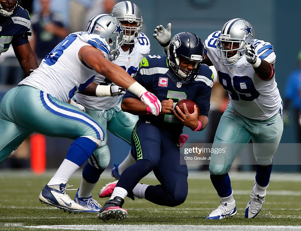 Quarterback Russell Wilson #3 of the Seattle Seahawks slides to the turf as defensive end Tyrone Crawford #98, defensive end Anthony Spencer #93 and defensive end George Selvie #99 of the Dallas Cowboys converge at CenturyLink Field on October 12, 2014 in Seattle, Washington.