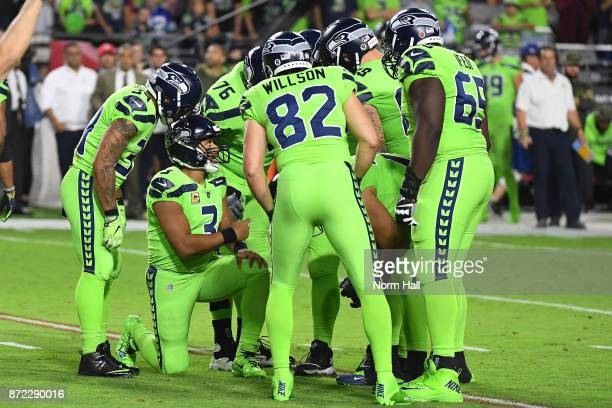 Quarterback Russell Wilson of the Seattle Seahawks talks to his team in a huddle in the first half of the NFL game against the Arizona Cardinals at...