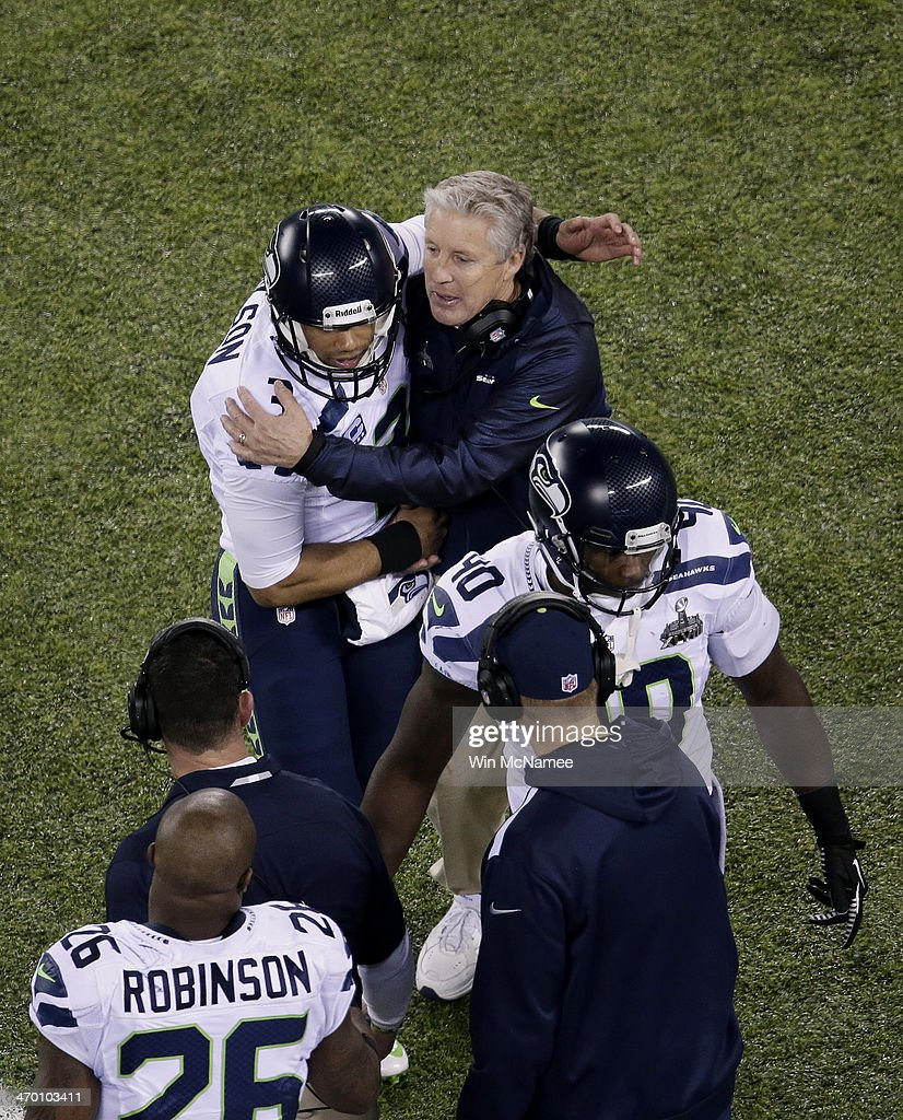 Quarterback Russell Wilson #3 of the Seattle Seahawks talks with head coach Pete Carroll of the Seattle Seahawks as he comes off field during Super Bowl XLVIII at MetLife Stadium on February 2, 2014 in East Rutherford, New Jersey.