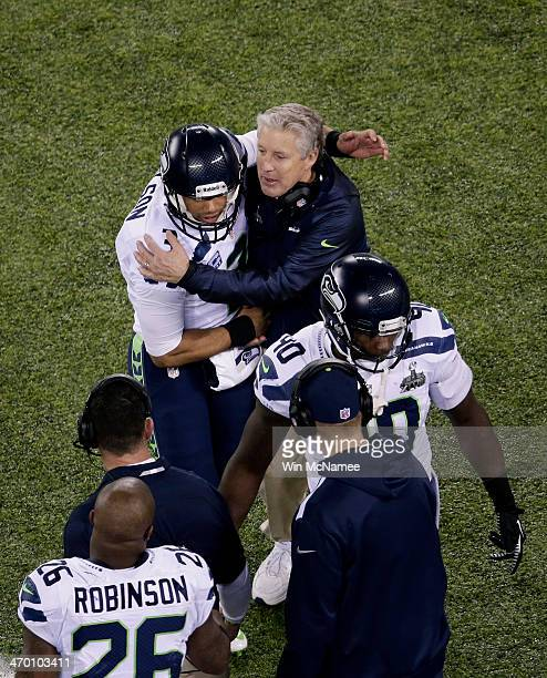 Quarterback Russell Wilson of the Seattle Seahawks talks with head coach Pete Carroll of the Seattle Seahawks as he comes off field during Super Bowl...