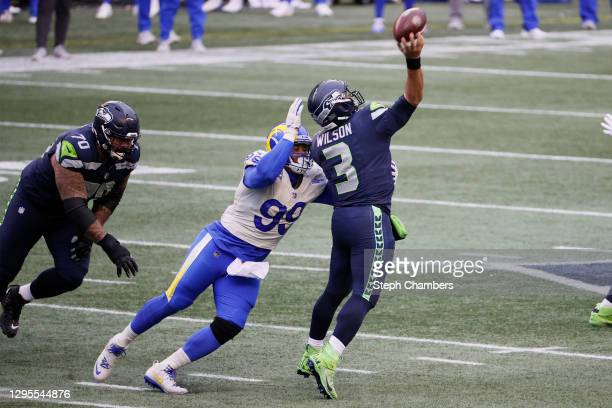 Quarterback Russell Wilson of the Seattle Seahawks throws a pass as he is pressured by defensive end Aaron Donald of the Los Angeles Rams during the...