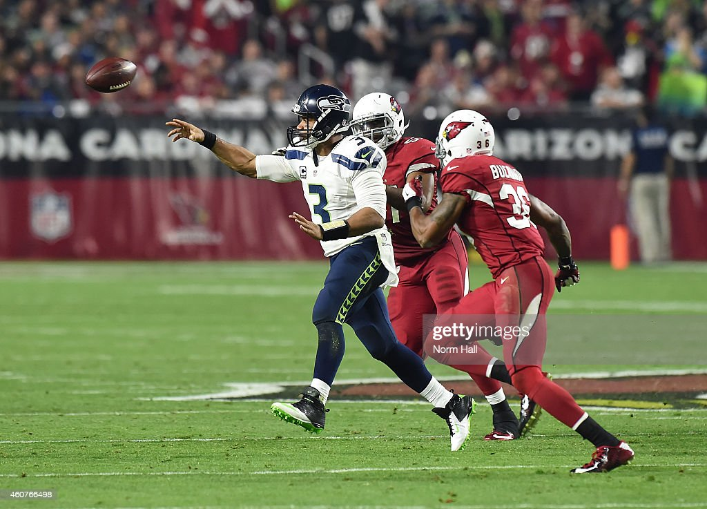 Quarterback Russell Wilson #3 of the Seattle Seahawks throws the football under pressure from strong safety Deone Bucannon #36 of the Arizona Cardinals at University of Phoenix Stadium on December 21, 2014 in Glendale, Arizona. The Seahawks won 35-6.