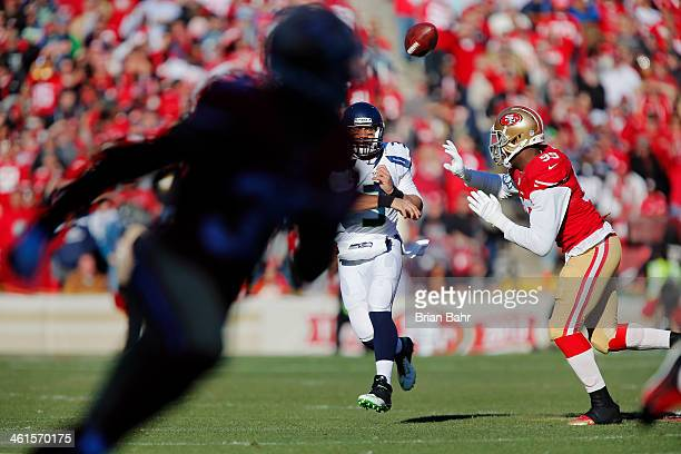 Quarterback Russell Wilson of the Seattle Seahawks throws to Golden Tate under pressure from linebacker Aldon Smith of the San Francisco 49ers in the...