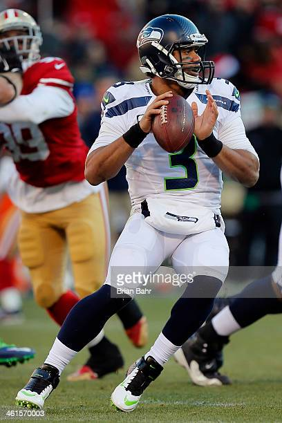 Quarterback Russell Wilson of the Seattle Seahawks throws to wide receiver Golden Tate for eight yards against the San Francisco 49ers in the third...