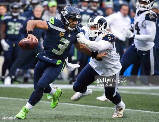 Quarterback Russell Wilson of the Seattle Seahawks tries to keep defensive tackle Aaron Donald of the Los Angeles Rams at bay in the 2nd quarter of...