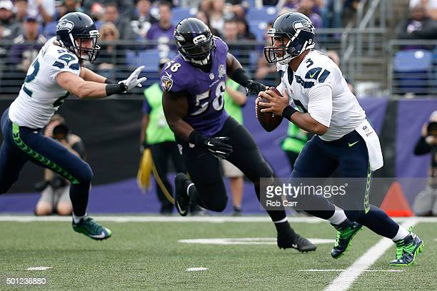 Quarterback Russell Wilson of the Seattle Seahawks works under pressure from outside linebacker Elvis Dumervil of the Baltimore Ravens while tight...