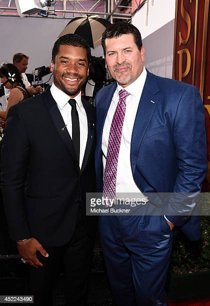 NFL quarterback Russell Wilson with TV analyst Mark Schlereth attends The 2014 ESPYS at Nokia Theatre LA Live on July 16 2014 in Los Angeles...