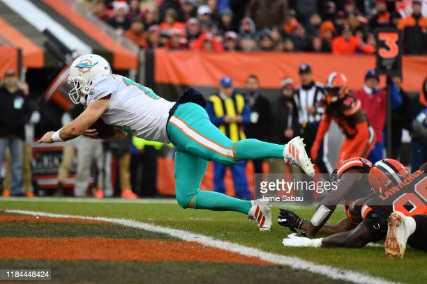 Quarterback Ryan Fitzpatrick of the Miami Dolphins dives into the end zone for an 8-yard touchdown run in the third quarter against the Cleveland...