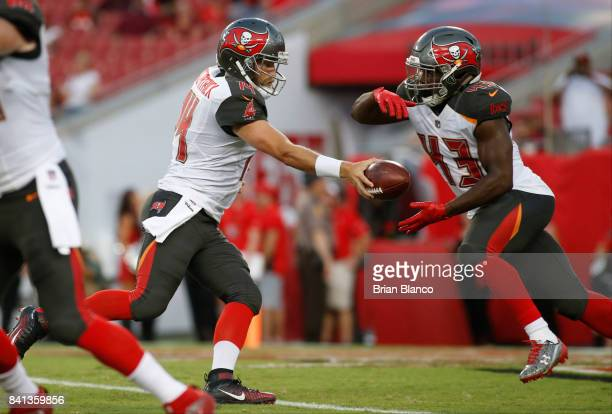 Quarterback Ryan Fitzpatrick of the Tampa Bay Buccaneers hands off to running back Peyton Barber during the first quarter of an NFL preseason...
