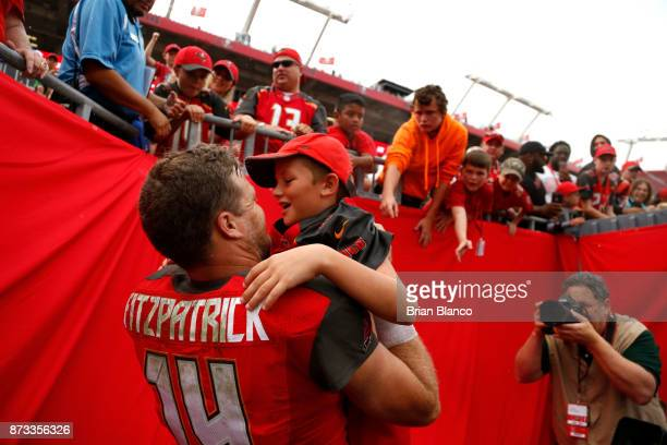 Quarterback Ryan Fitzpatrick of the Tampa Bay Buccaneers pulls on of his children out of the stands following the Buccaneers' 1510 win over the New...