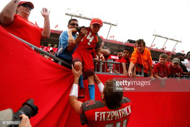 Quarterback Ryan Fitzpatrick of the Tampa Bay Buccaneers pulls one of his children out of the stands following the Buccaneers' 1510 win over the New...