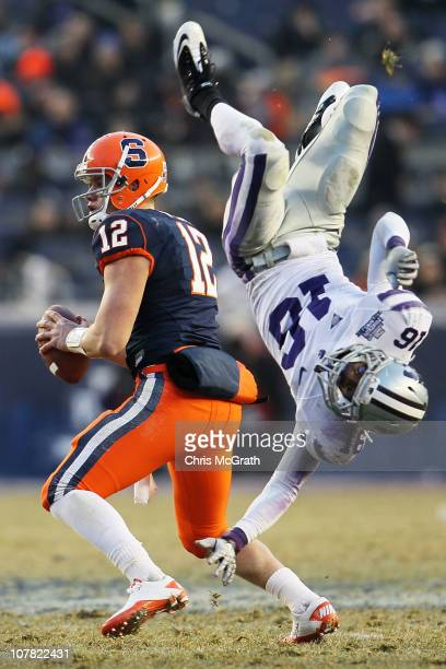 Quarterback Ryan Nassib of the Syracuse Orange gets around a diving tackle by Terrence Sweeney of the Kansas State Wildcats during the New Era...