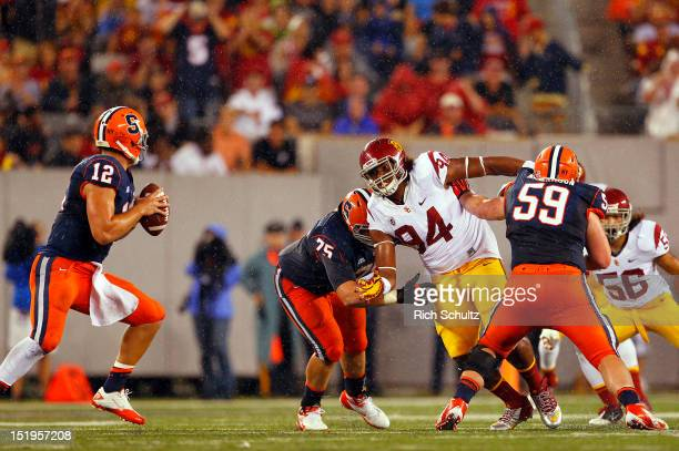 Quarterback Ryan Nassib of the Syracuse Orange looks to pass as Leonard Williams of the USC Trojans breaks through the blocking of Zack Chibane and...