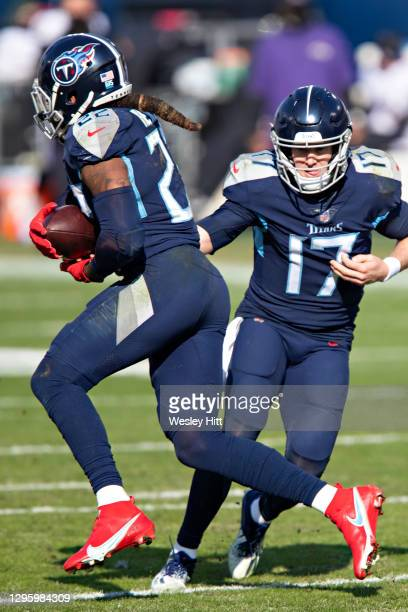Quarterback Ryan Tannehill hands off the ball to running back Derrick Henry of the Tennessee Titans during their AFC Wild Card Playoff game against...