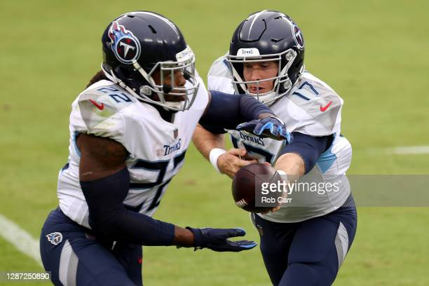 Quarterback Ryan Tannehill hands the ball off to running back Derrick Henry of the Tennessee Titans in the first half against the Baltimore Ravens at...