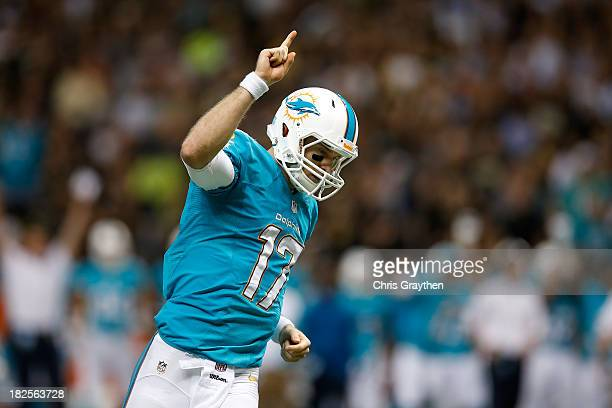 Quarterback Ryan Tannehill of the Miami Dolphins celebrates after running back Lamar Miller scores on a fiveyard touchdown run in the second quarter...