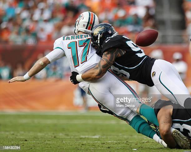 Quarterback Ryan Tannehill of the Miami Dolphins fumbles against Defensive Tackle Jeris Pendleton of the Jacksonville Jaguars at Sun Life Stadium on...