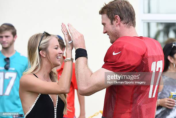Quarterback Ryan Tannehill of the Miami Dolphins high fives his wife Lauren Tannehill after practice at Nova Southeastern University on August 9 2015...