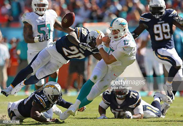 Quarterback Ryan Tannehill of the Miami Dolphins loses the ball after being hit by cornerback Chris Davis of the San Diego Chargers in the second...