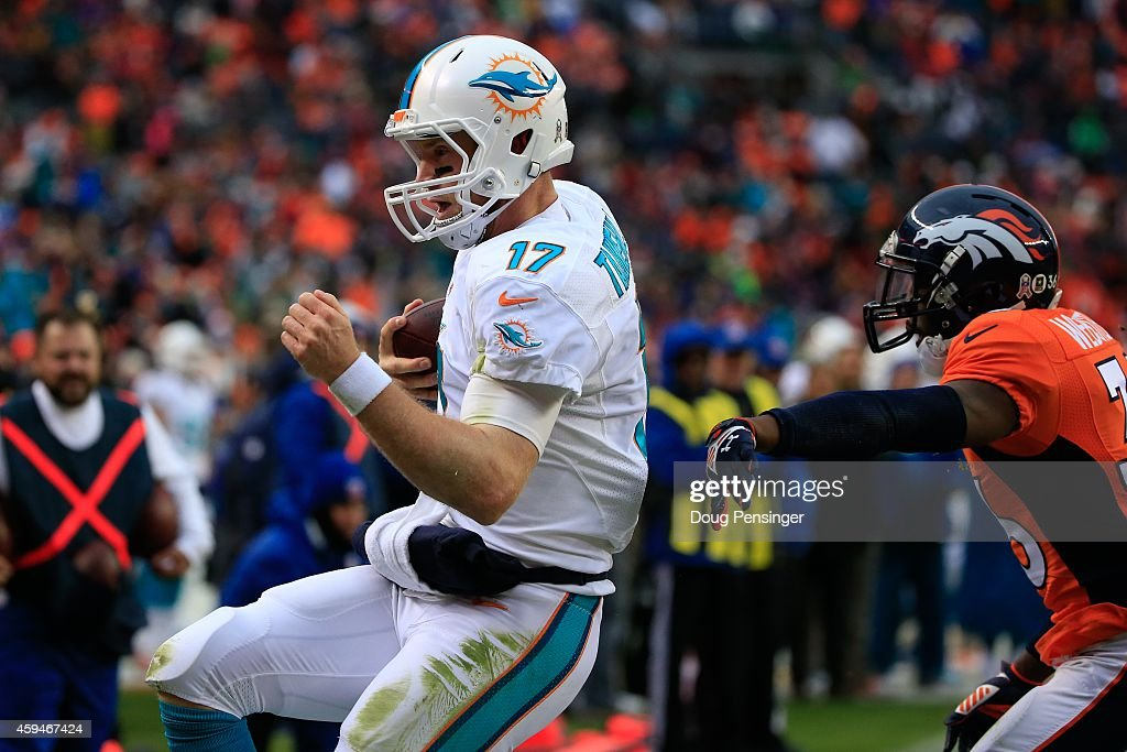 Quarterback Ryan Tannehill #17 of the Miami Dolphins scores on a 1-yard second quarter rushing touchdown against the Denver Broncos during a game at Sports Authority Field at Mile High on November 23, 2014 in Denver, Colorado.