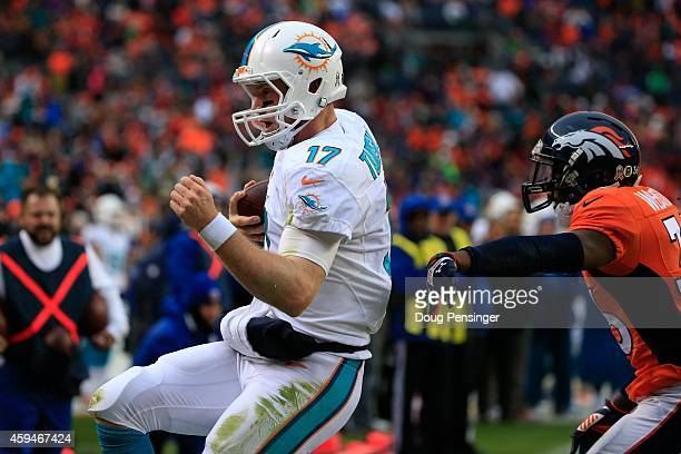 Quarterback Ryan Tannehill of the Miami Dolphins scores on a 1yard second quarter rushing touchdown against the Denver Broncos during a game at...