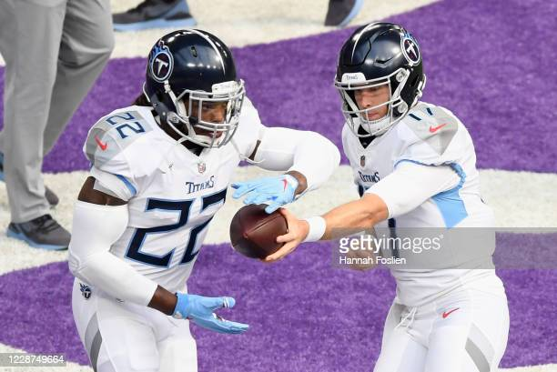 Quarterback Ryan Tannehill of the Tennessee Titans hands the ball to teammate Derrick Henry during warm-ups before the game against the Minnesota...
