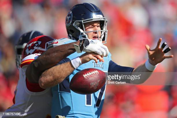 Quarterback Ryan Tannehill of the Tennessee Titans is hit by defensive end Chris Jones of the Kansas City Chiefs as he forces the fumble in the first...