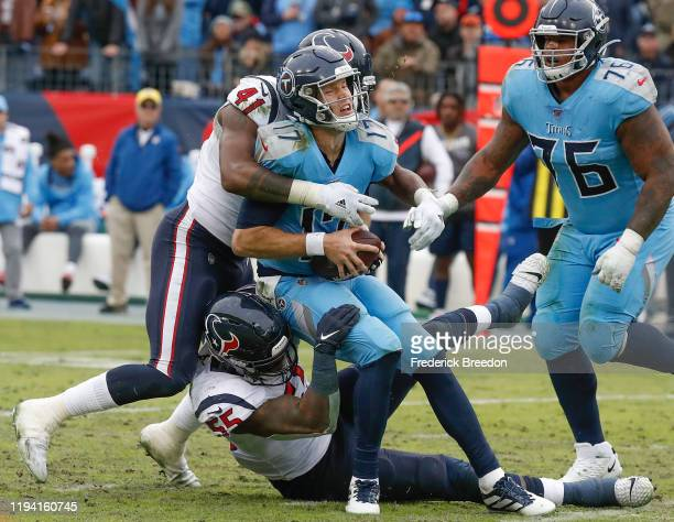 Quarterback Ryan Tannehill of the Tennessee Titans is sacked by Zach Cunningham of the Houston Texans during the second half at Nissan Stadium on...