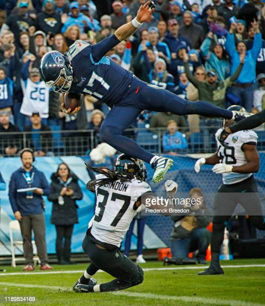 Quarterback Ryan Tannehill of the Tennessee Titans jumps over Tre Herndon of the Jacksonville Jaguars for a touchdown during the first half at Nissan...