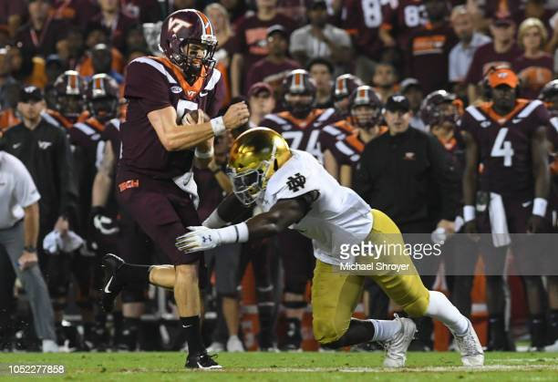 Quarterback Ryan Willis of the Virginia Tech Hokies is hit during a rushing attempt by linebacker Te'von Coney of the Notre Dame Fighting Irish in...
