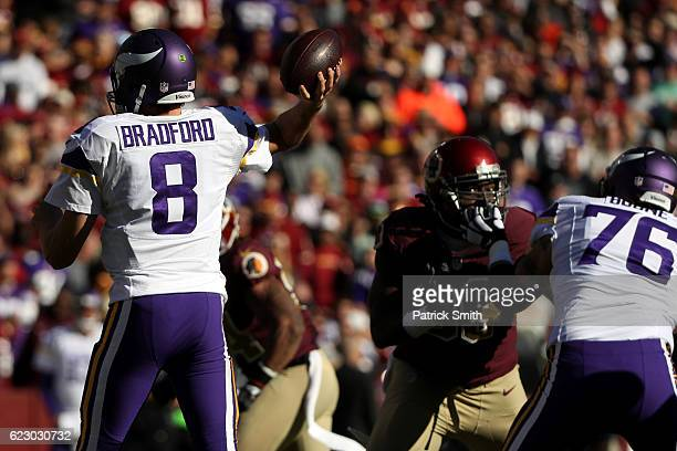 Quarterback Sam Bradford of the Minnesota Vikings passes the ball while teammate offensive guard Alex Boone blocks against defensive end Ricky Jean...
