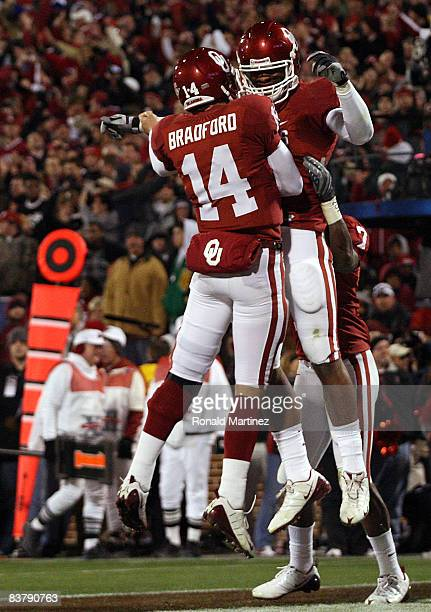 Quarterback Sam Bradford of the Oklahoma Sooners celebrates a touchdown with Jermaine Gresham during play against the Texas Tech Red Raiders in the...