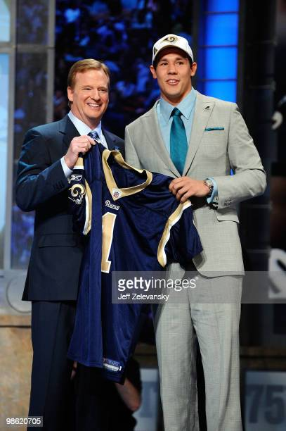 Quarterback Sam Bradford of the Oklahoma Sooners holds up a St Louis Rams jersey as he stands with NFL Commissioner Roger Goodell after Bradford was...