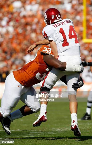Quarterback Sam Bradford of the Oklahoma Sooners is tackled by Lamarr Houston of the Texas Longhorns at Cotton Bowl on October 17 2009 in Dallas Texas