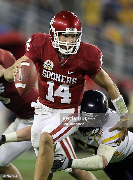 Quarterback Sam Bradford of the Oklahoma Sooners looks to throw the ball as a West Virginia Mountaineers defender dives at his legs at the Tostito's...