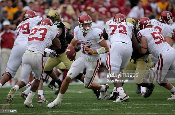 Quarterback Sam Bradford of the Oklahoma Sooners rolls out from behind the protection of his teammates as they face the Colorado Buffaloes at Folsom...