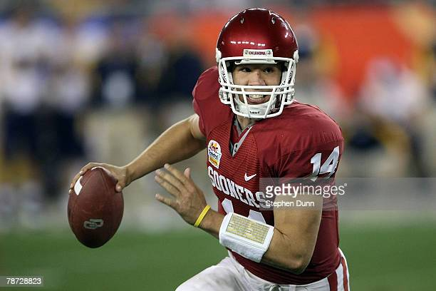 Quarterback Sam Bradford of the Oklahoma Sooners scrambles in the first half against the West Virginia Mountaineers at the Tostito's Fiesta Bowl at...