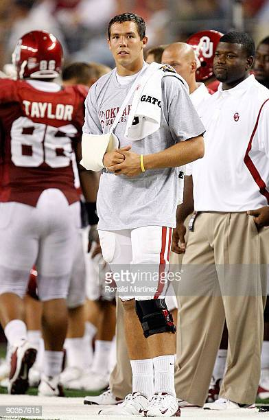 Quarterback Sam Bradford of the Oklahoma Sooners stands on the sidelines after suffering an injury against the Brigham Young Cougars at Cowboys...