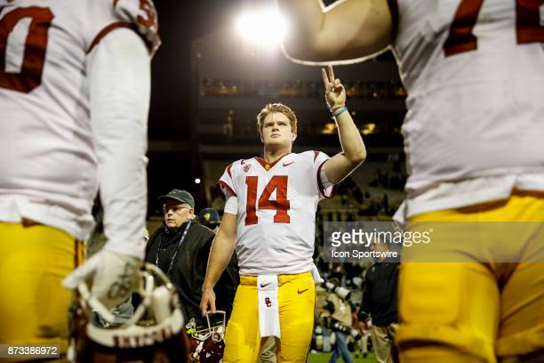USC quarterback Sam Darnold holds up a victory sign with teammates as the marching band plays the USC fight song after the Colorado Buffalos game...