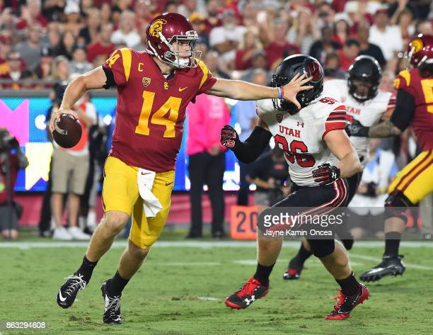 Quarterback Sam Darnold of the USC Trojans avoids pressure from defensive end Nick Heninger of the Utah Utes as he looks for an open receiver in the...
