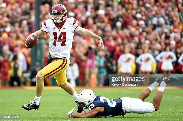 Quarterback Sam Darnold of the USC Trojans runs with the ball as cornerback John Reid of the Penn State Nittany Lions attempts to tackle him in the...