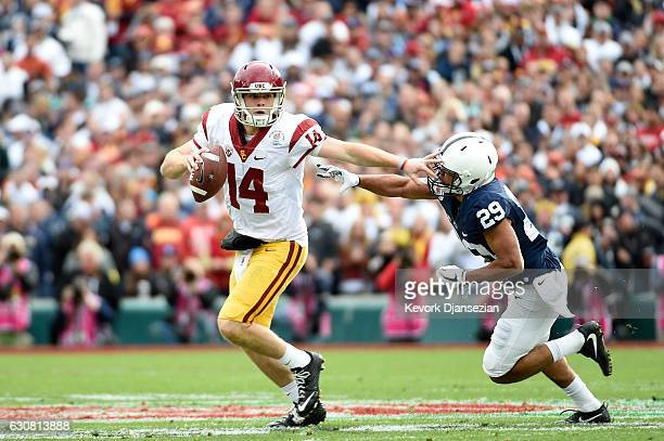 Quarterback Sam Darnold of the USC Trojans stiff arms cornerback John Reid of the Penn State Nittany Lions in the first half of the 2017 Rose Bowl...